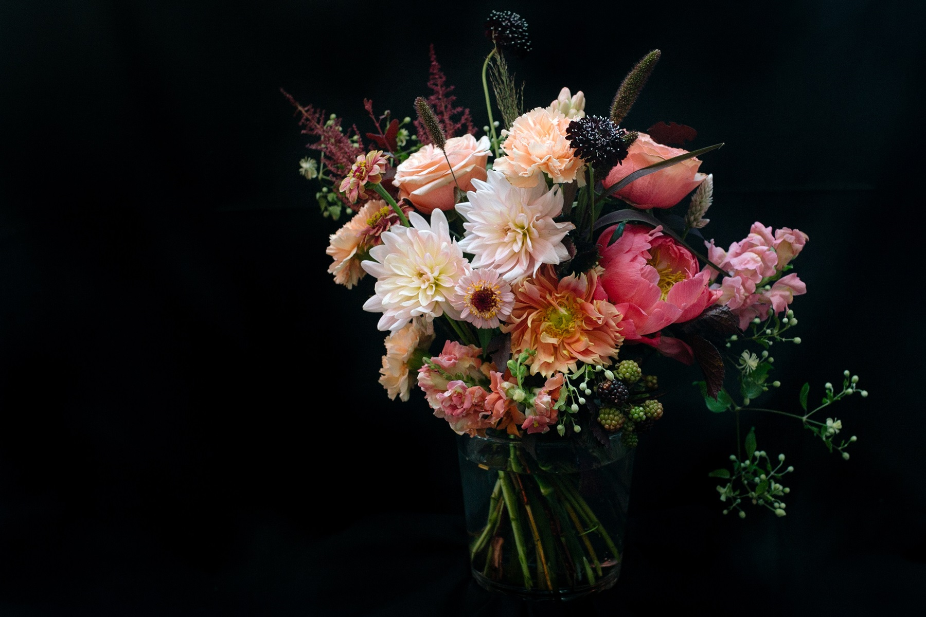 Lush bouquet in garden style with delicate roses, pink anthurium, dahlias and seasonal berries